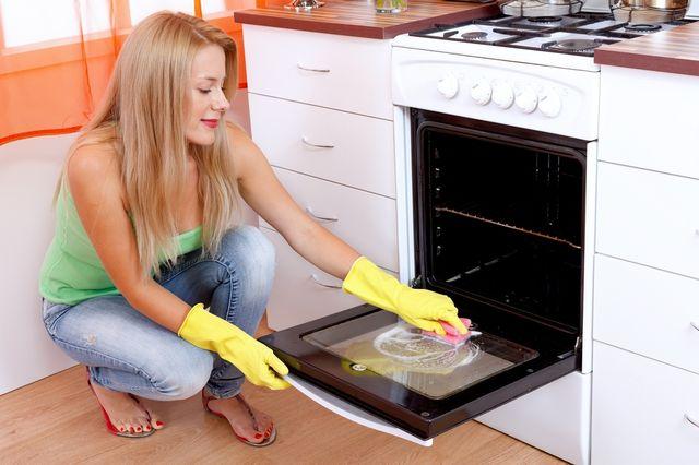 Женщина моет духовку